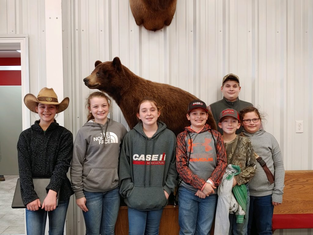 7 youth posing with a bear at a 4-H contest